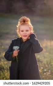 a curly haired blonde girl with a tuft of hair in the background light blows a dandelion in a coat in a meadow in the autumn