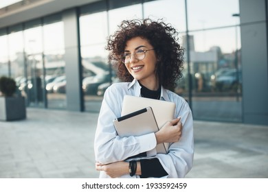Curly haired business lady is embracing and holding a laptop while posing with glasses in front of a building