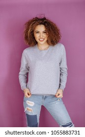 Curly haired girl with freckles in blank grey sweatshirt on violet background. Mock up.