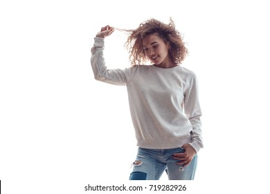 Curly haired girl with freckles in blank grey sweatshirt on white background. Mock up.