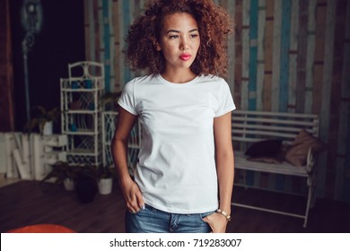 Curly haired girl with freckles in blank white t-shirt. Mock up.