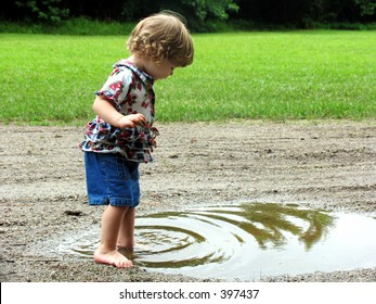 Curly haired little girl playing in a mud puddle