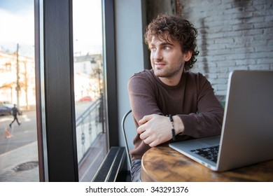 Curly handsome attractive content pensive happy young man sitting in cafe with laptop and enjoying the view