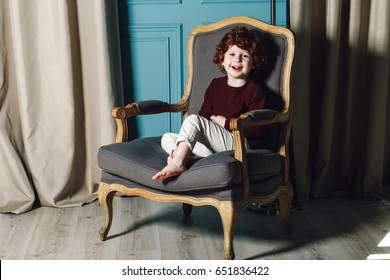 curly little boy in burgundy sweater and white pants sitting in an armchair and smiling at camera