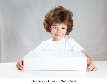 Curly little cute boy with a white box in his hands tenderly looking at the camera. Gray background. Close-up.