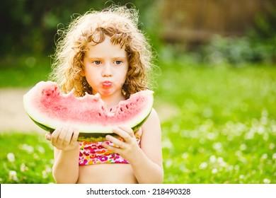 Curly little girl eating watermelon in summer park. Instagram filter.
