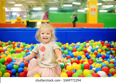 Curly little girl having fun in ball pit with colorful balls. Child playing on indoor playground. Kid jumping in ball pool.