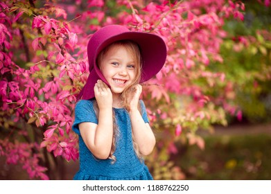 Curly little girl with rose tree in autumn