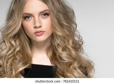 Curly long hair woman blonde hairstyle near white wall