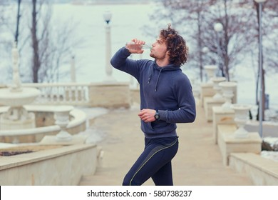 Curly Male runner drinks water from a bottle in park on the stai