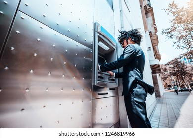 Curly man entrepreneur in a formal suit and in sunglasses is using his bank card to withdraw deposit money from his account using street ATM terminal; a young businessman is using the cash dispenser