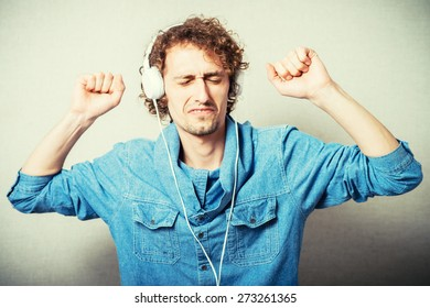 curly man listening to music on headphones white, dancing