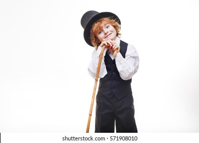 curly red-haired boy, handsome, stylishly dressed boy with red hair in a hat, child with a cane in his hand dressed in a black suit isolated on white background, little actor.