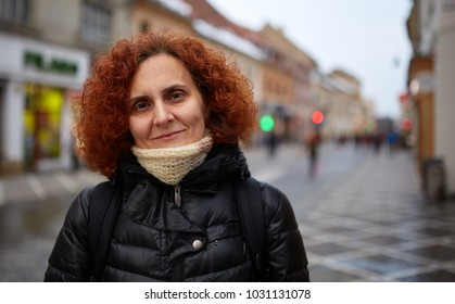 A curly redhead middle aged woman in an old town