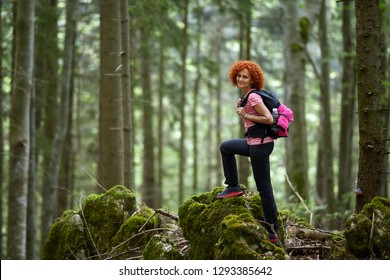 Curly redhead woman with backpack hiking on a trail