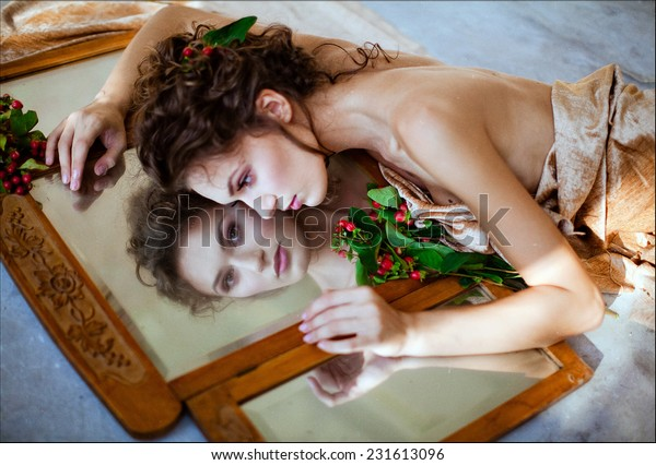 Curly sensual girl lying about a mirror, reflecting in it and near red berry
