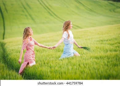 curly sisters twins walking on wheat sunny field. Family happiness and understanding. Happy Friends walking in sunny weather outdoors.
