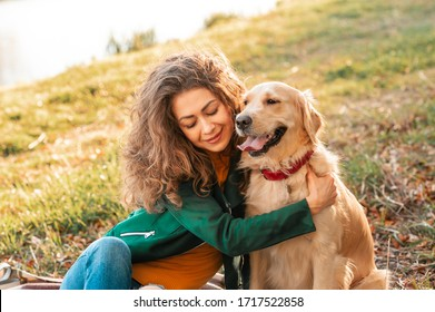 Curly smiling girl embrance her pet dog near face. Golden retriever dog playing with a curly woman walking outdoors sunny day. love and care for the pet.