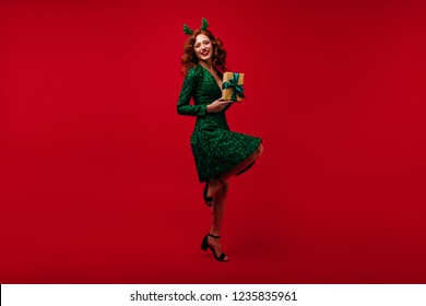 Curly white lady in party attire posing with new year present. Laughing ginger woman relaxing at christmas event.