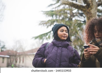 curly woman standing in park with friend and using smartphone – winter day, technology, curiosity