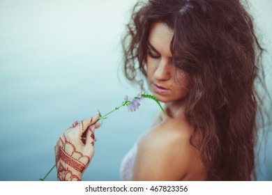 Curly woman touches her face with delicate violet flower
