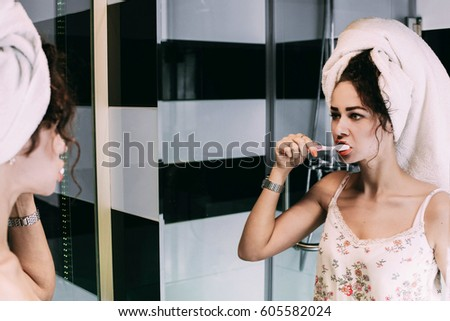Curly woman with towel on her head cleans her teeth