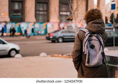 Curly young boy with backpack walking on the street copy space