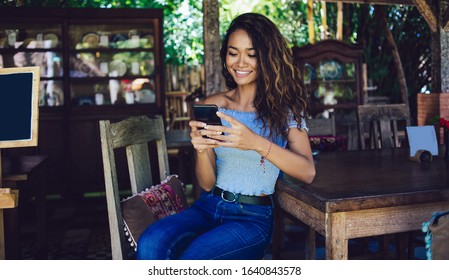 Curly young female Indonesian messaging on phone sitting on chair leaning on wooden table on outside veranda in ethnic style smiling
