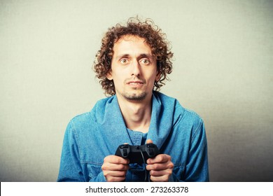 Curly young man playing video game winner. On a gray background