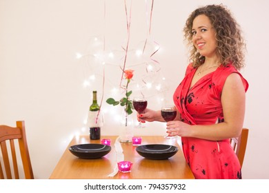 Curly young woman set table for romantic dinner with wine for her boyfriend on Valentines Day