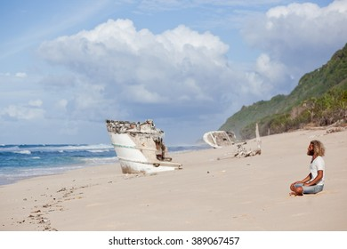 curly-bearded man is sitting on the background of the beach and the ship's wreckage