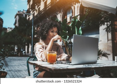 A curly-hair dazzling young African-American female freelancer is working with her project on the laptop remotely from a city cafe outdoors, with a glass of delicious fresh juice near on the table