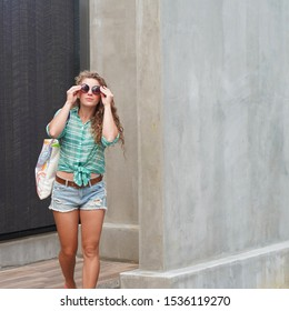 curly-haired blonde model in the background of concrete walls in round glasses. emotional girl in denim shorts, waving hand, laughing. lifestyle fashion