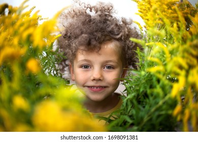 Curly-haired boy smiles among yellow flowers. Art portrait.
