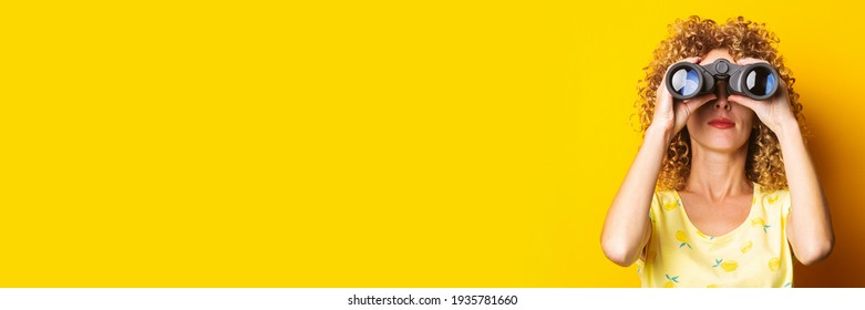 curly-haired girl looks through binoculars on a bright yellow background. Banner