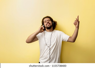 A curly-headed man wearing white T-shirt is listening to music and making a horn gesture with his hand. Lovely mood and bliss.