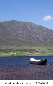 Currach moored to a tyre offshore with mountain ridge in the background