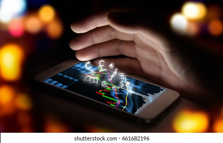 Currencies sign icon and smartphone with stock market graph screen and hand with bokeh blur background.  Blockchain , Fintech Investment Financial Internet Technology Concept.