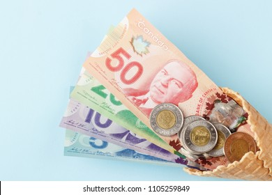 Currency: Canadian banknotes and coins on the blue background