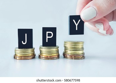 Currency Concept: JPY (Japanese Yen) text stacked on coins with cool image temperature