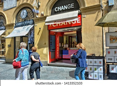 Currency exchange. Banking industry in West Europe. Red sign and currency rate table in an exchange office of Italian bank. People walk along the street. Italy, Florence – April 17, 2018