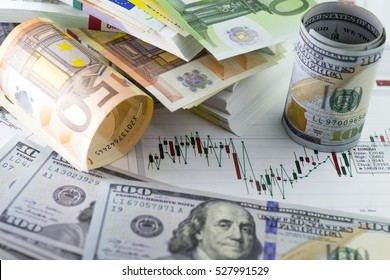 Currency exchange trading. Hundred us dollar bill in foreground. Piles of euro banknotes in background. Currency us eur exchange chart under the bills. fifty euro banknote, hundred dollar bill rolled