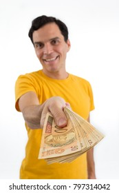 Currency: real. Exchange. Happy man is handing out money. Loan. Receiving. Credit. He is wearing a yellow jersey. Isolated on white background. Focus on money.