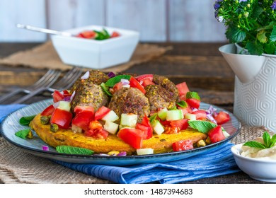 Curried chickpea cake with pistachio lamb meatballs and tomato sambal