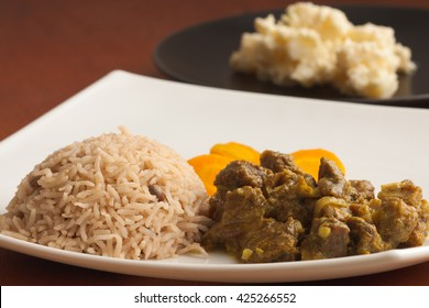 Curried Goat served with Rice and Peas, carrots and homemade potato salad