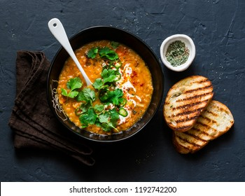 Curried red lentil tomato and coconut soup - delicious vegetarian food on dark background, top view