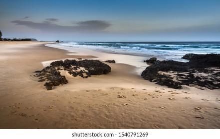 Currumbin Gold Coast Australia early morning sandy beach sunrise footprints rocky shore ocean waves coastal calm cloudy