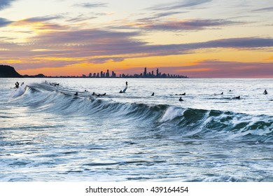Currumbin Rock Gold Coast sunset ocean wave and surfer silhouettes