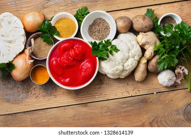 Curry cauliflower raw ingredients for cooking on wooden background top view