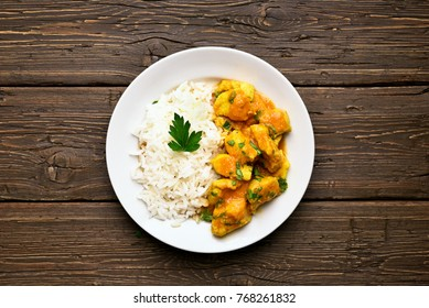 Curry chicken with rice on plate over wooden background. Top view, flat lay.